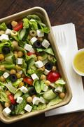 Stock Photo of Greek Salad to Go; Plastic Fork and Small Container of Dressing