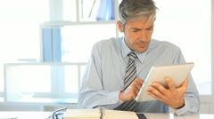 businessman using electronic tablet in office - stock footage