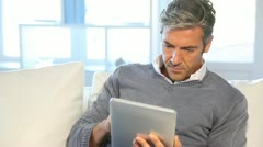 man sitting in sofa at home with electronic tablet - stock footage