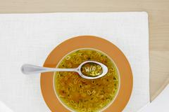 Clear broth with vegetables and alphabet noodles Stock Photos