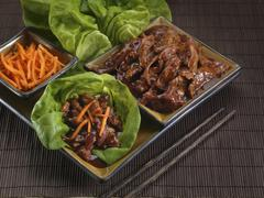 Oriental pork with carrot strips on lettuce leaves - stock photo