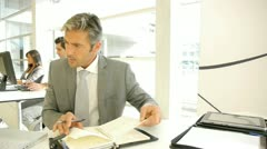 Businessman writing on agenda in office Stock Footage