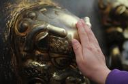 Stock Photo of hand touching bronze lion head.