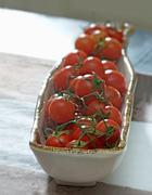 Tomatoes (still on the stem) in a ceramic dish - stock photo