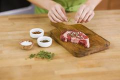 Woman Seasoning a Steak Stock Photos