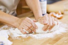 Woman Kneading Dough on Floured Counter in Kitchen Stock Photos