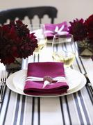A place setting with a white plate and a pink napkin Stock Photos