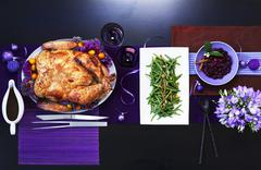 Chinese roasted turkey with green beans on a table with purple decorations - stock photo
