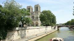 Bateau-mouche cruising by notre dame of paris cathedral Stock Footage