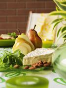 Cheese platter with brie, almonds, baby spinach and pears Stock Photos
