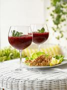 Chicken Satay and berry ice cream with mint in stemware glasses - stock photo