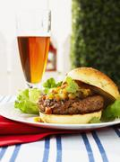 Curried lamb burger with mango chutney and beer Stock Photos