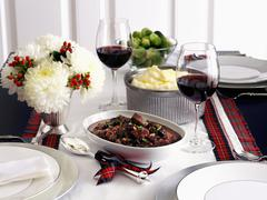 Saddle of venison, mashed potatoes and Brussels sprouts on a table decorated for Stock Photos
