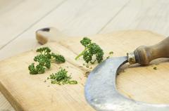 Parsley and chopping knife on a wooden cutting board - stock photo