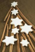Cinnamon sticks forming the shape of a Christmas tree with cinnamon stars on top - stock photo