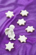Cinnamon stars and an angel figurine on a purple surface Stock Photos