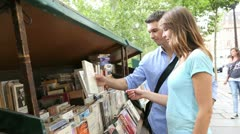 Couple in paris looking at booksellers Stock Footage