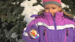 Child Holding a Fireworks in her Hand in front of a Decorated Christmas Tree Stock Footage