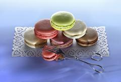 Different types of macaroons, stacked, on a cake paper placemat - stock photo