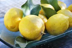 Fresh lemons with leaves on a platter - stock photo