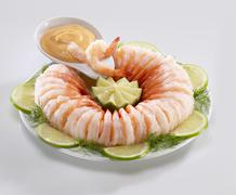 Ring of shrimp with cocktail sauce, limes and dill - stock photo