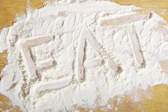 The word 'eat' written in flour Stock Photos