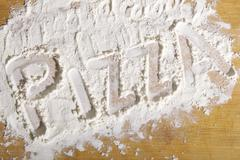 The word 'pizza' written in flour Stock Photos