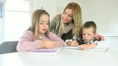 Woman helping chidren with homework Stock Footage