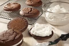 Making Whoopie Pies; Adding Cream Filling To the Whoopie Pies - stock photo
