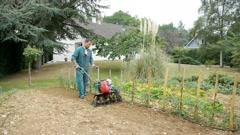 Gardener using motorized cultivator Stock Footage