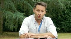 Man sitting in garden talking to camera Stock Footage