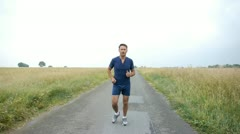 Man jogging on country road Stock Footage