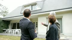 real-estate agent with senior couple buying new house - stock footage