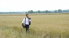 Businessman walking in wheat field Stock Footage