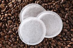 Three coffee pads on coffee beans - stock photo