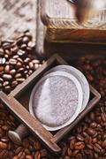 Coffee pads, a coffee mill and coffee beans - stock photo