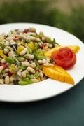 Bowl of White Bean Salad with Papaya Garnish Stock Photos