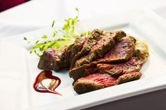 Sliced Beef Tenderloin with Potatoes on a White Plate Stock Photos
