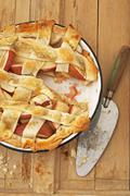 Apple Lattice Crust Pie with Slice Removed; On Wooden Surface with Knife; From - stock photo