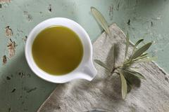 A bowl of olive oil and an olive sprig Stock Photos