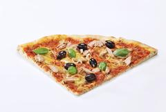 A slice of pizza with tuna, olives and basil - stock photo