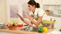 Woman cooking with electronic pad Stock Footage