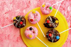 Pop cakes with icing sugar and coloured chocolate beans Stock Photos