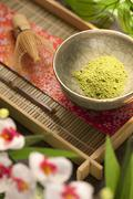 Stock Photo of Japanese Matcha Green Tea Powder in a Bowl on Tray; Flowers