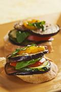 Slices of Bread Topped with Sliced Eggplant, Zucchini, Tomato and Yellow Pepper Stock Photos
