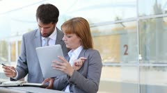 Business people working outside on electronic tablet Stock Footage