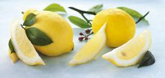 Whole lemons, lemon wedges and lemon leaves - stock photo