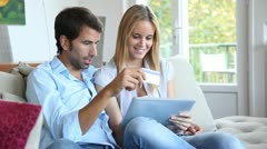 Young couple at home doing online shopping Stock Footage
