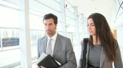 Business people walking in building hallway Stock Footage
