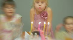 Little girl blows candles on birthday cake, photo flashes Stock Footage